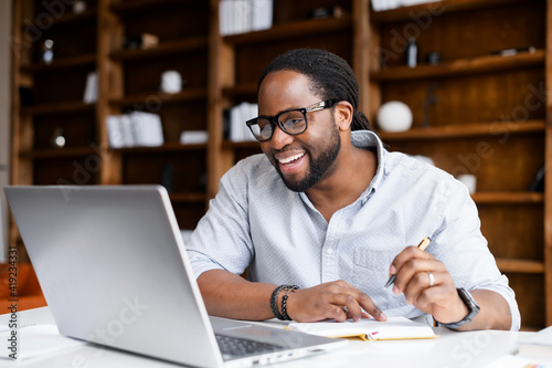 Obraz Smiling African-American guy takes notes watching webinars on the laptop,researching business tasks, a male student is studying online, listening video lectures, writes down, e-learning concept - fototapety do salonu