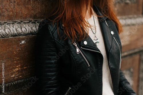 Obraz girl in a black leather jacket posing against a wall background - fototapety do salonu