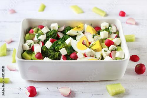 Fototapeta Wiosenna sałatka z brokułem, jajkiem, serem feta, ogórkiem i rzodkiewką obraz