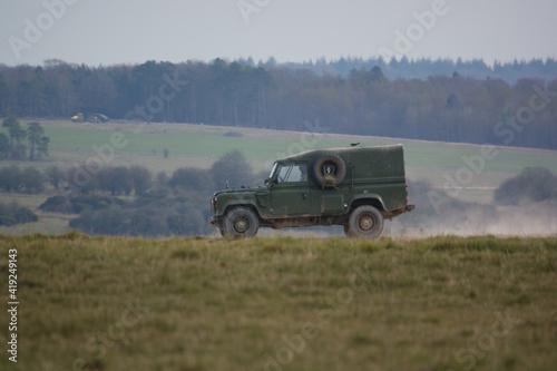 british army land rover defender kicking up dust along a track Fotobehang