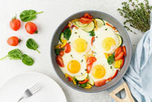 Fried Eggs Poached With Vegetables On Teflon Pan - Pepper, Tomatoes, Spinach, Peppers, Onion And Garlic. Mediterranean Cousine. Keto Meal, FODMAP Recipe, Low Carb. Top View
