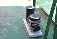 Rusty Mooring Post With Ship Ropes On An Old Ferry. Bollard With Mooring Lines On The Ship.