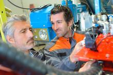Two Mechanics Reparing Old Agrimotors At Farm