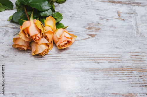 Fototapeta Bouquet of yellow roses on a wooden table with space for text obraz na płótnie