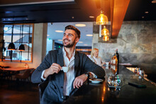 Smiling Middle-aged Man In Formal Wear Sitting In The Bar And Drinking His Morning Coffee.