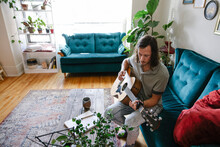 Young Man Playing Guitar At Home On Couch