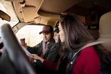 Family Looking At Map In Front Seats Of RV