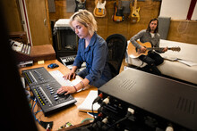 Man And Woman Working Together In Music Recording Studio