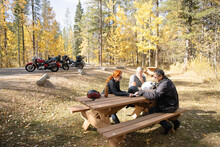 Bikers Taking A Break At Picnic Table In Forest