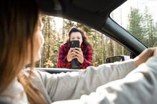 Woman Taking Photo Of Friend Inside Car