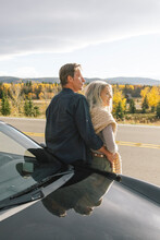 Couple Leaning On Sports Car In Front Of Forest