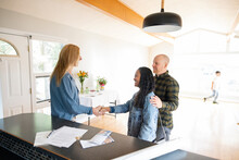 Realtor Shaking Hands With Couple At Open House