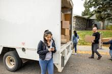 Teenage Girl Using Smart Phone At Back Of Moving Van