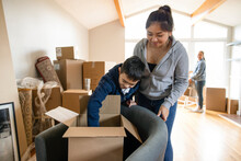 Brother And Sister Unpacking Box In New Home