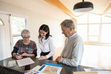 Realtor Helping Senior Couple Sign Sales Contract In New Home