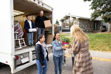 Realtor Surprising Family With Flowers At Moving Van Outside New Home