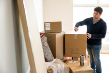 Man Unpacking Cardboard Moving Box In New Home