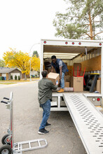 Male Movers Unloading Cardboard Box From Moving Van