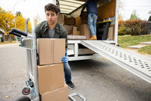 Male Mover Lifting Cardboard Box From Hand Truck At Back Of Moving Van