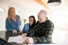 Happy Realtor Watching Couple Sign New Home Sales Contract