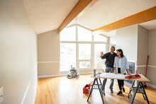 Architect And Client Discussing Blueprints In Home Under Renovation