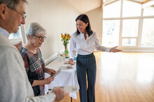 Friendly Realtor Greeting Senior Couple With Brochures At Open House