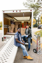 Portrait Male Movers Taking A Break At Back Of Moving Van