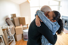 Happy Couple Hugging And Moving Into New House