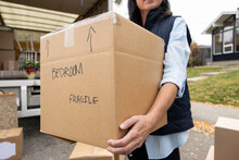 Close Up Woman Carrying Cardboard Box Labeled Fragile