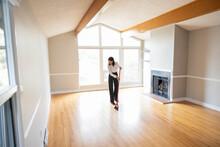 Female Realtor Sweeping Hardwood Floors In Empty Home Living Room