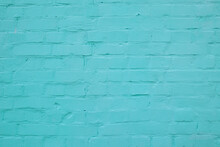 The Texture Of The Building Facade Of A Brick Wall From Rows Of Bricks Painted In Turquoise Color