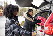 Mother And Daughter Unloading Christmas Presents From Car