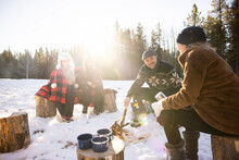 Family Making Fire In Snowy Forest
