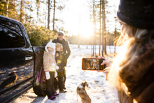 Woman Taking Photo Of Family Choosing Christmas Tree In Woods
