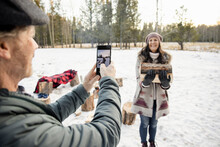 Man Taking Photo Of Wife Carrying Firewood In Snow