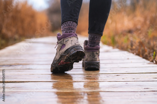 Obraz na plátně girl's feet walking on wooden boardwalk with hiking boots on rainy day