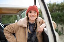 Portrait Happy Young Woman In Knit Hat At Camper Van Doorway