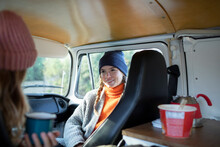 Young Women Friends Relaxing In Camper Van On Road Trip