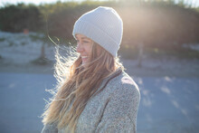 Beautiful Happy Young Woman In Knit Hat On Sunny Beach