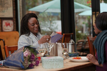 Mother And Daughter Celebrating Birthday At Cafe Table