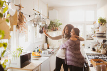 Happy Mother And Daughter Taking Selfie In Sunny Kitchen