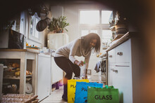 Young Woman Sorting Recycling On Kitchen Floor