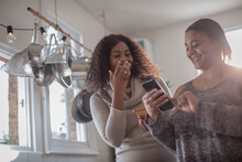 Happy Mother And Daughter Using Smart Phone In Kitchen