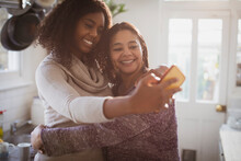 Happy Mother And Daughter Hugging And Taking Selfie In Kitchen
