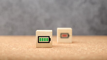 Green Battery Icon On A Wooden Cube With Blurred Red One Beyond Showing A Full And Empty Charge In A Power And Energy Concept
