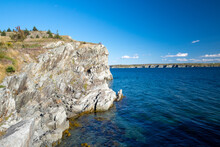 A Hiking Trail Along The Ocean With Waves Crashing On The Jagged Rocks. The Calm Water And Sky Are Blue With White Clouds. There Are Trees, Rocks, Grass, And Eroding Cliff Along The Edge Of The Ocean