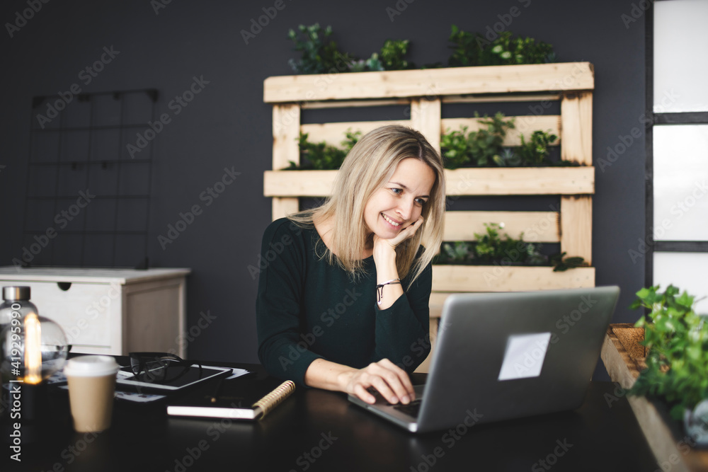 Fototapeta pretty blond young woman is sitting in an ecological office with lots of plants and is working on her laptop and is wearing a green sweater, concept sustainability and environment today