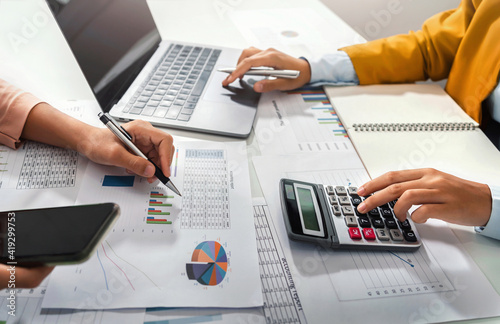 Obraz close up hand accountant holding pen pointing on paperwork chart for meeting team in office room. concept finance and accounting - fototapety do salonu