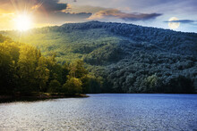 Day And Night Time Change Concept On A Lake Among Beech Forest In Summer. Beautiful Nature Landscape In Mountains. Vihorlat National Park With Sun And Moon On The Sky