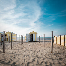 Vintage Yellow And White Beach Hut Against Blue Sky.